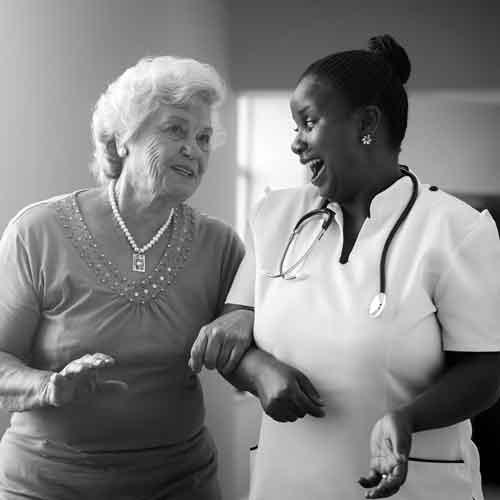 Nurse walking arm-in-arm with elderly lady laughing while having a conversation