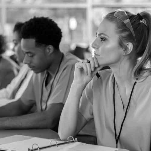 a young man and young lady in scrubs sitting in a classroom