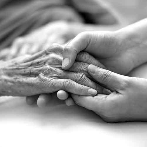 younger hands holding an elderly hands over a blanket on a bed